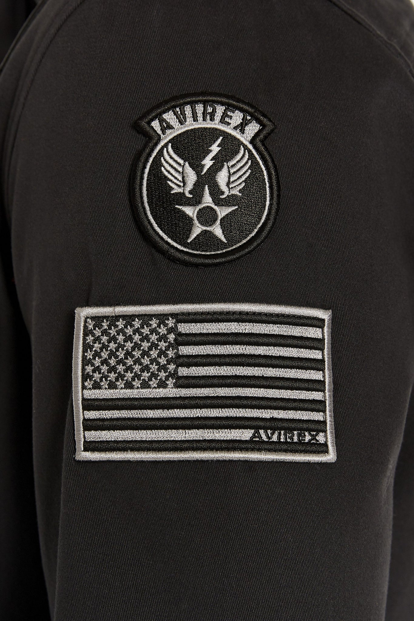 Detailed view of embroidery white logo and patch on the right arm