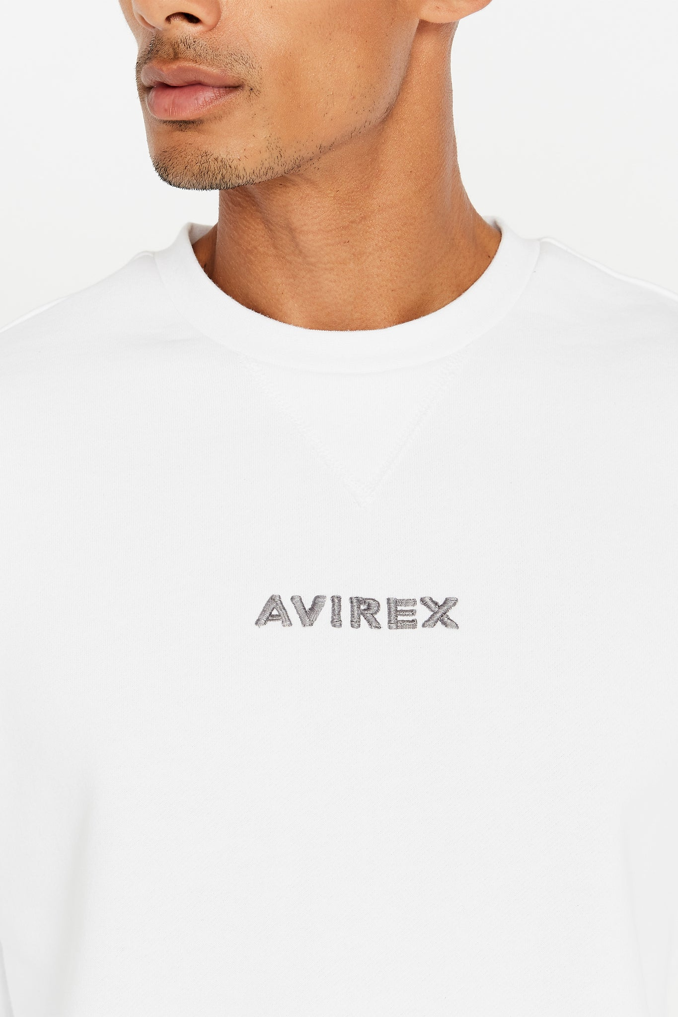 Detailed view of front light grey embroidered logo saying Avirex