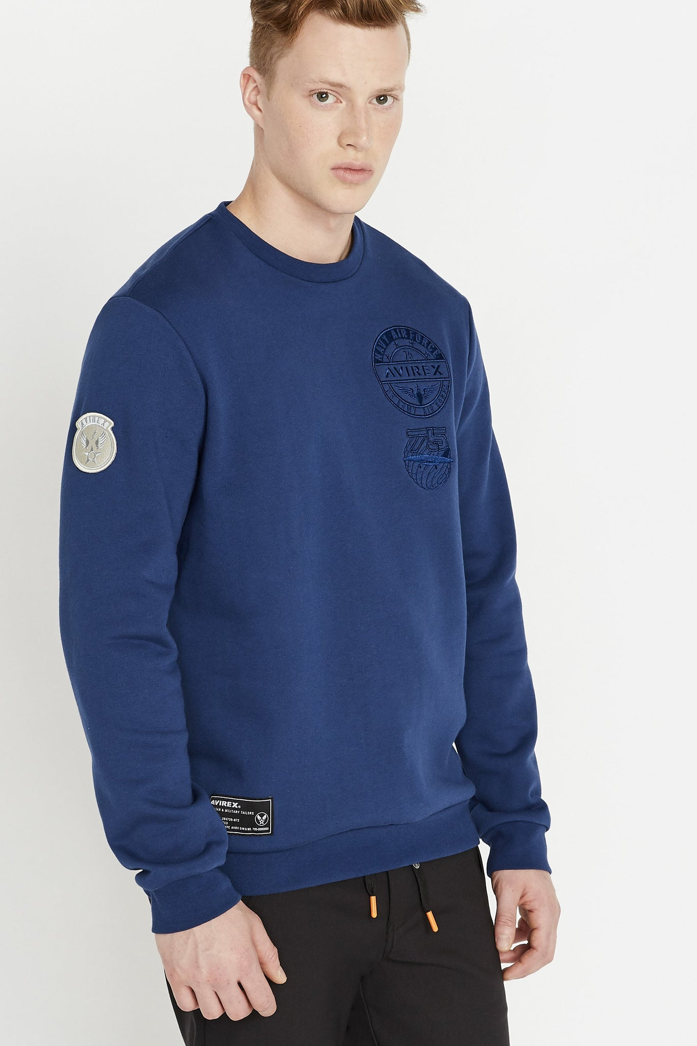 Side view of men wearing a blue long sleeve crew neck sweater with embroidery on chest and patch on right bottom and on the right sleeve