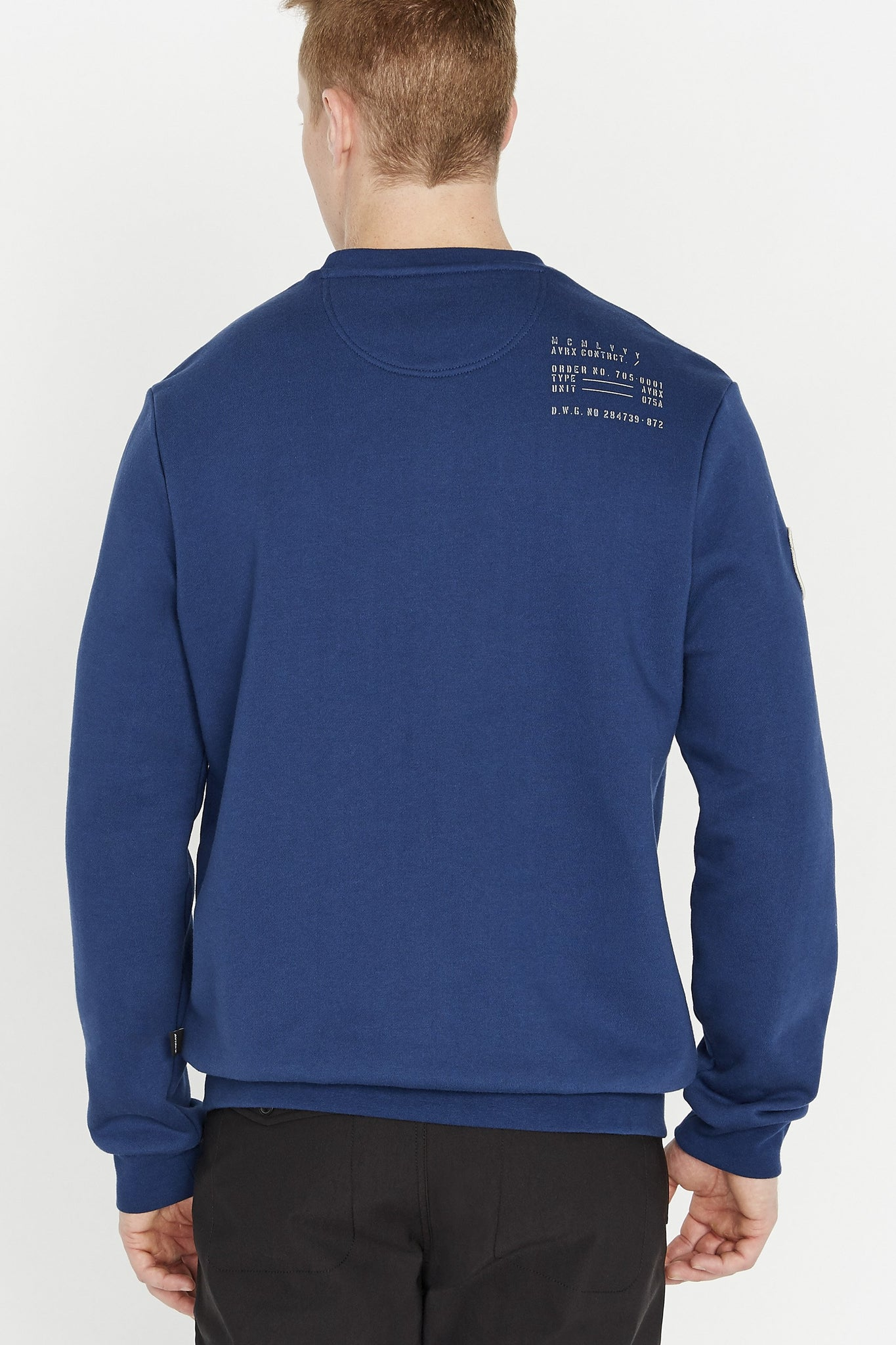 Back view of men wearing a blue long sleeve crew neck sweater with utility print on back shoulder