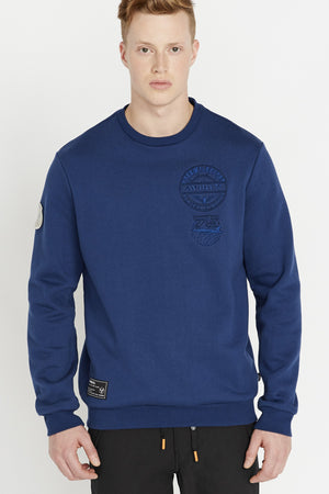 Men wearing a blue long sleeve crew neck sweater with embroidery on chest and patch on right bottom