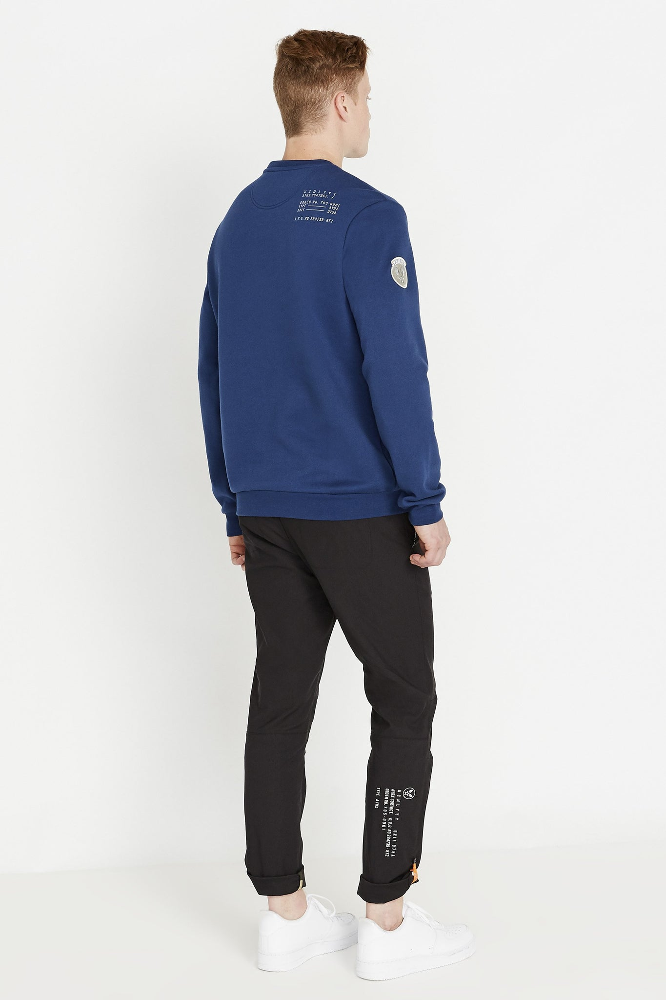 Back full view of men wearing a blue long sleeve crew neck sweater with utility print on back shoulder and black pants