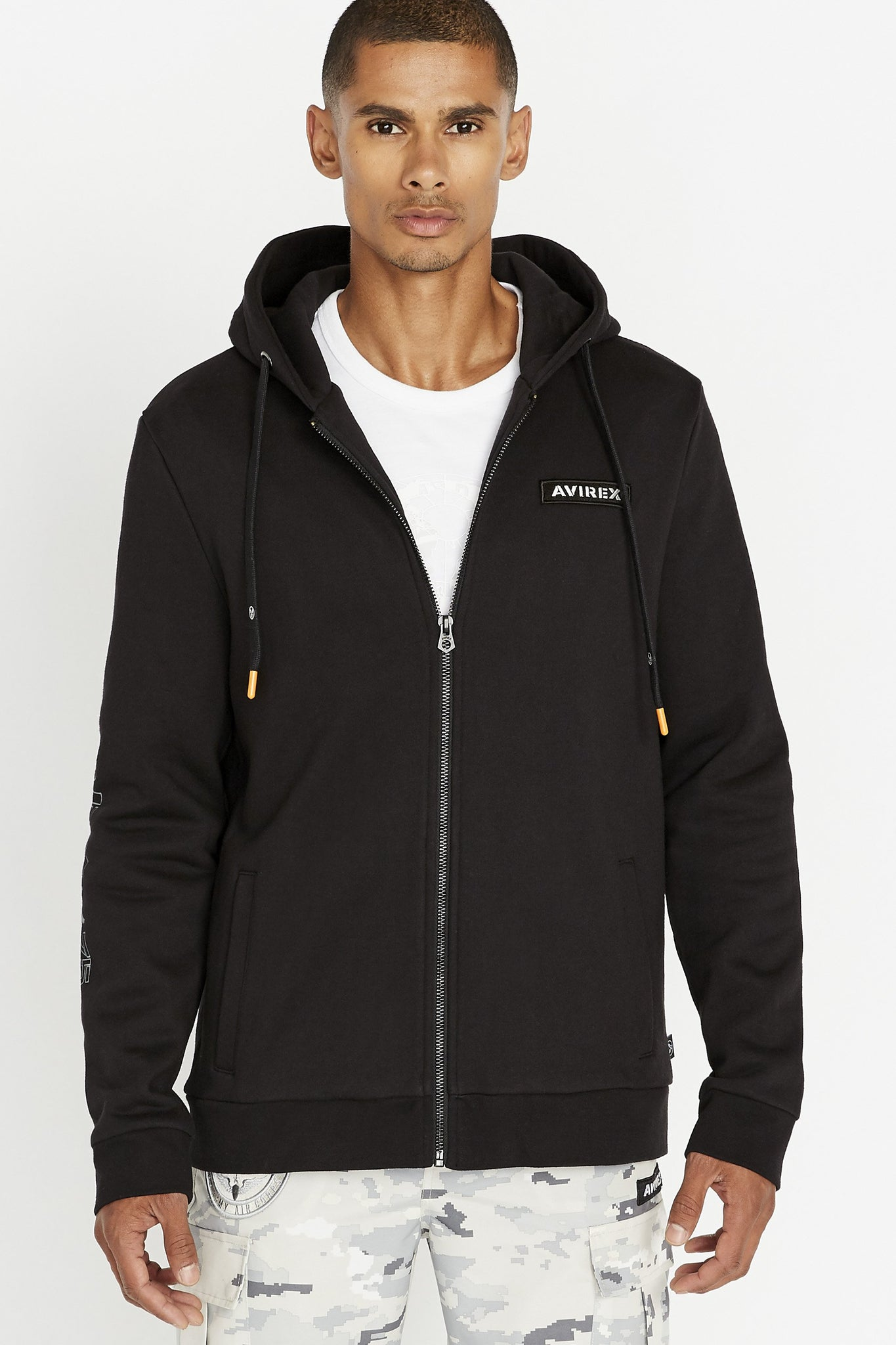 Men wearing a black long sleeve front zip hoodie sweatshirt with Avirex chest patch