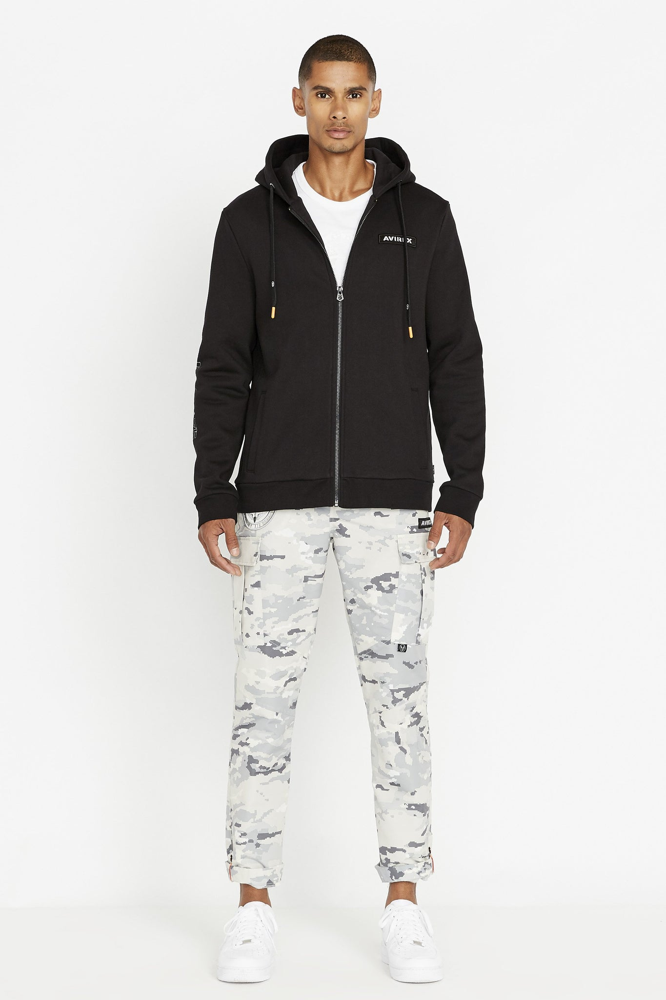 Full view of men wearing a black long sleeve front zip hoodie sweatshirt with Avirex chest patch and light grey camo print pants