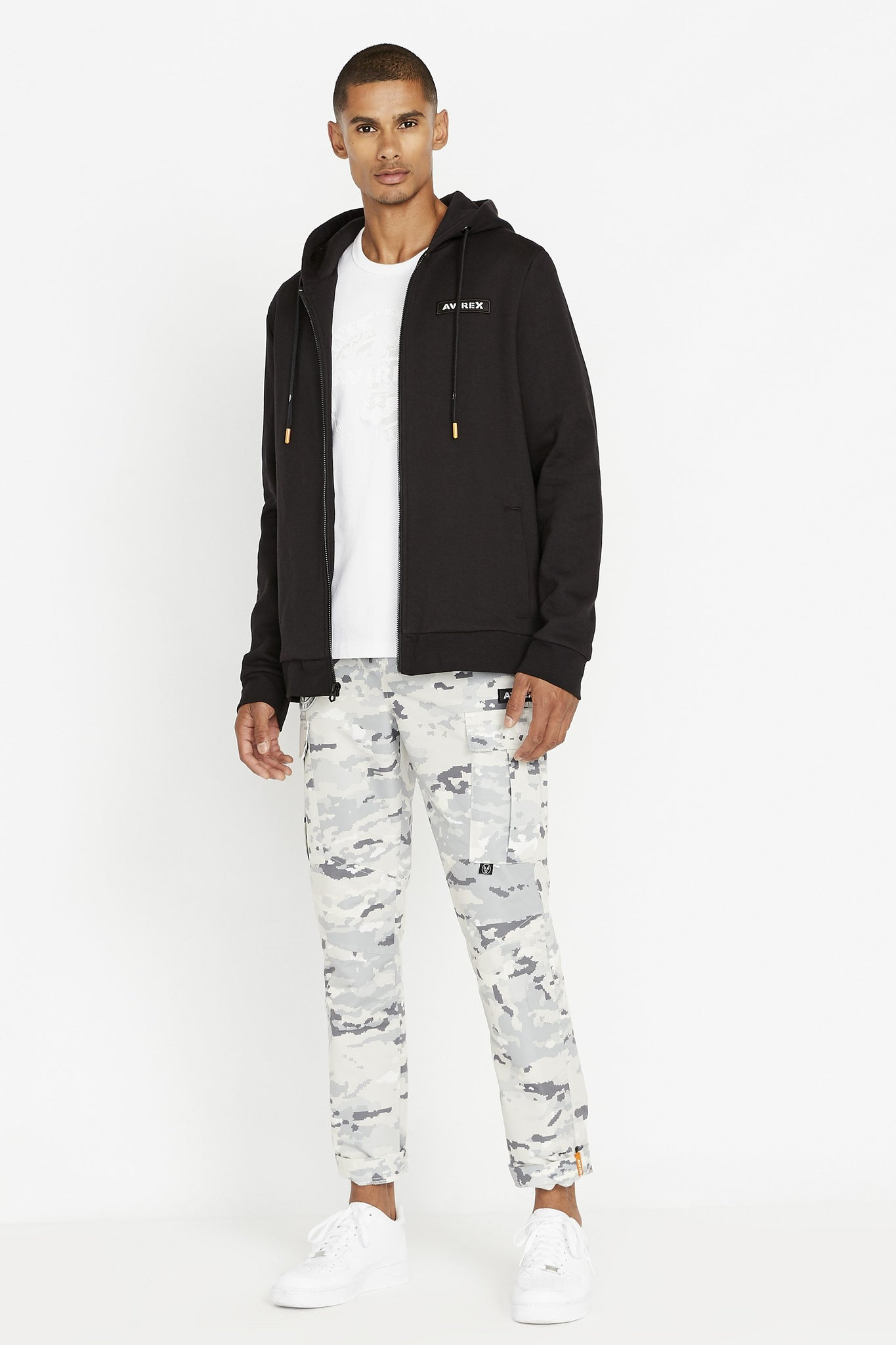 Full view of men wearing a black long sleeve front zip hoodie sweatshirt with Avirex chest patch and white crew neck t-shirt inside and light grey camo print pants