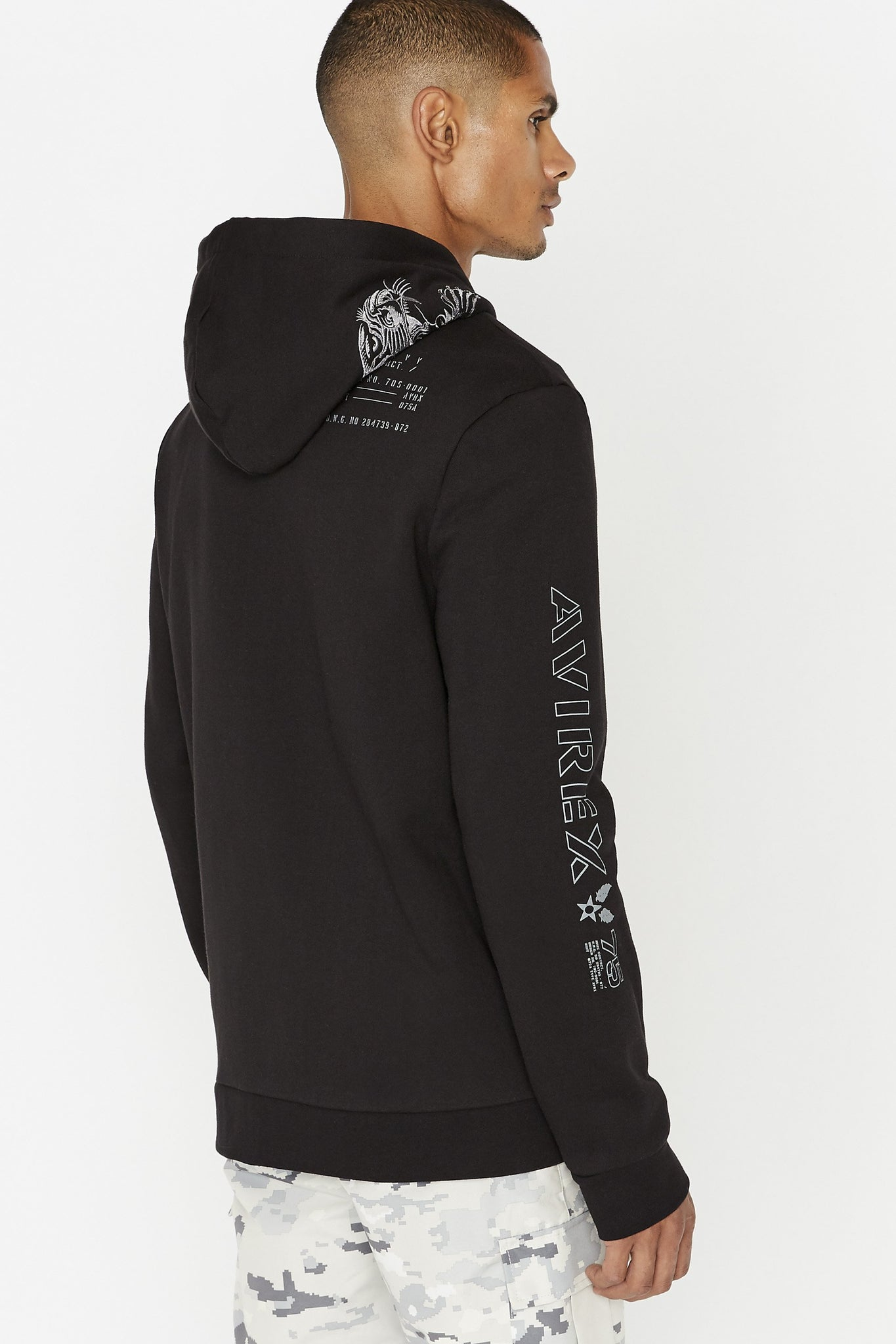 Side view of men wearing a black long sleeve sweatshirt with embroidered tiger on hood and print on back shoulder and on the right sleeve