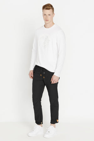 Side view of men wearing a white long sleeve crew neck T-shirt with white round logo graphic print on chest and black pants