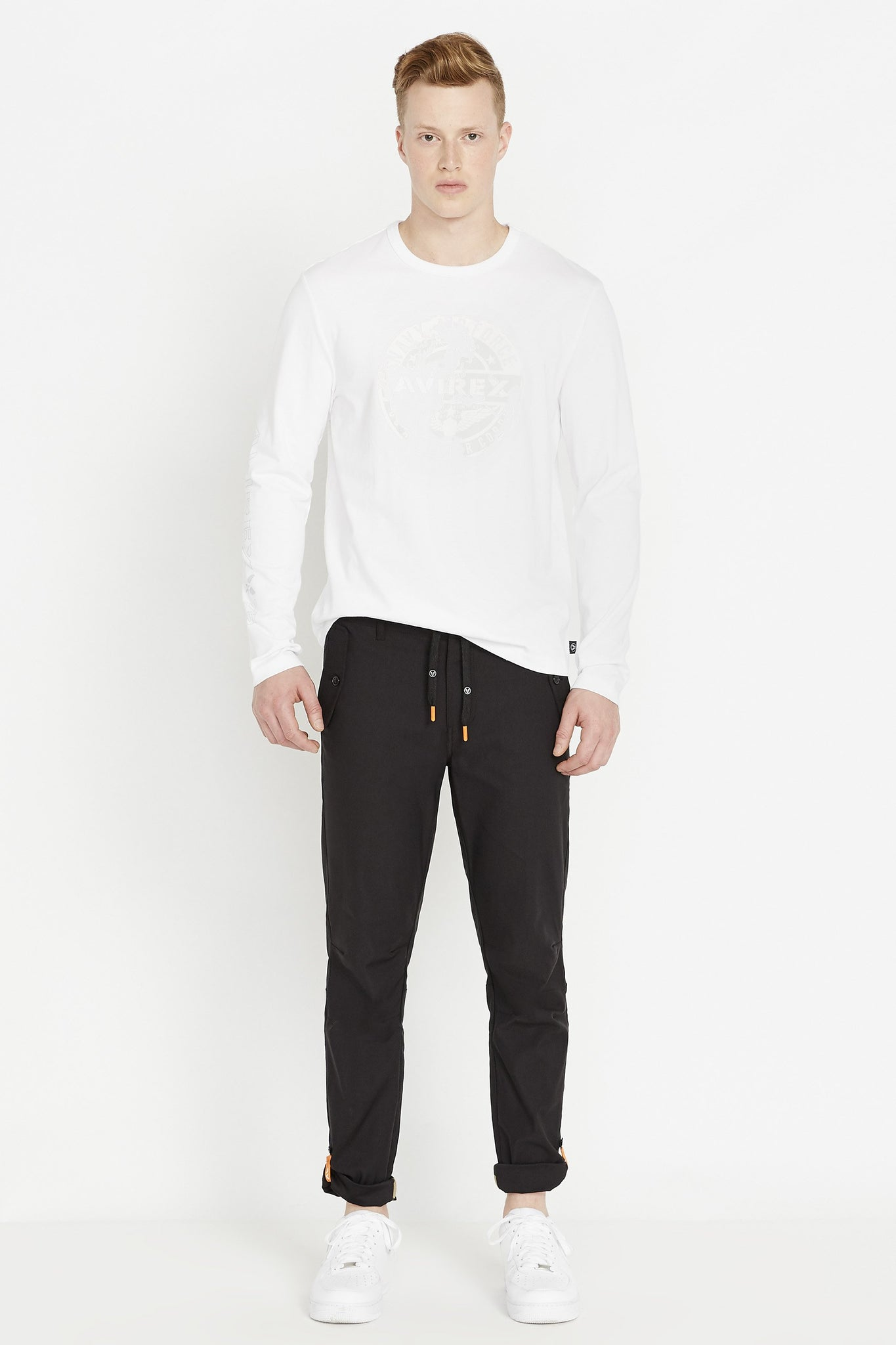 Full view of men wearing a white long sleeve crew neck T-shirt with white round logo graphic print on chest and black pants