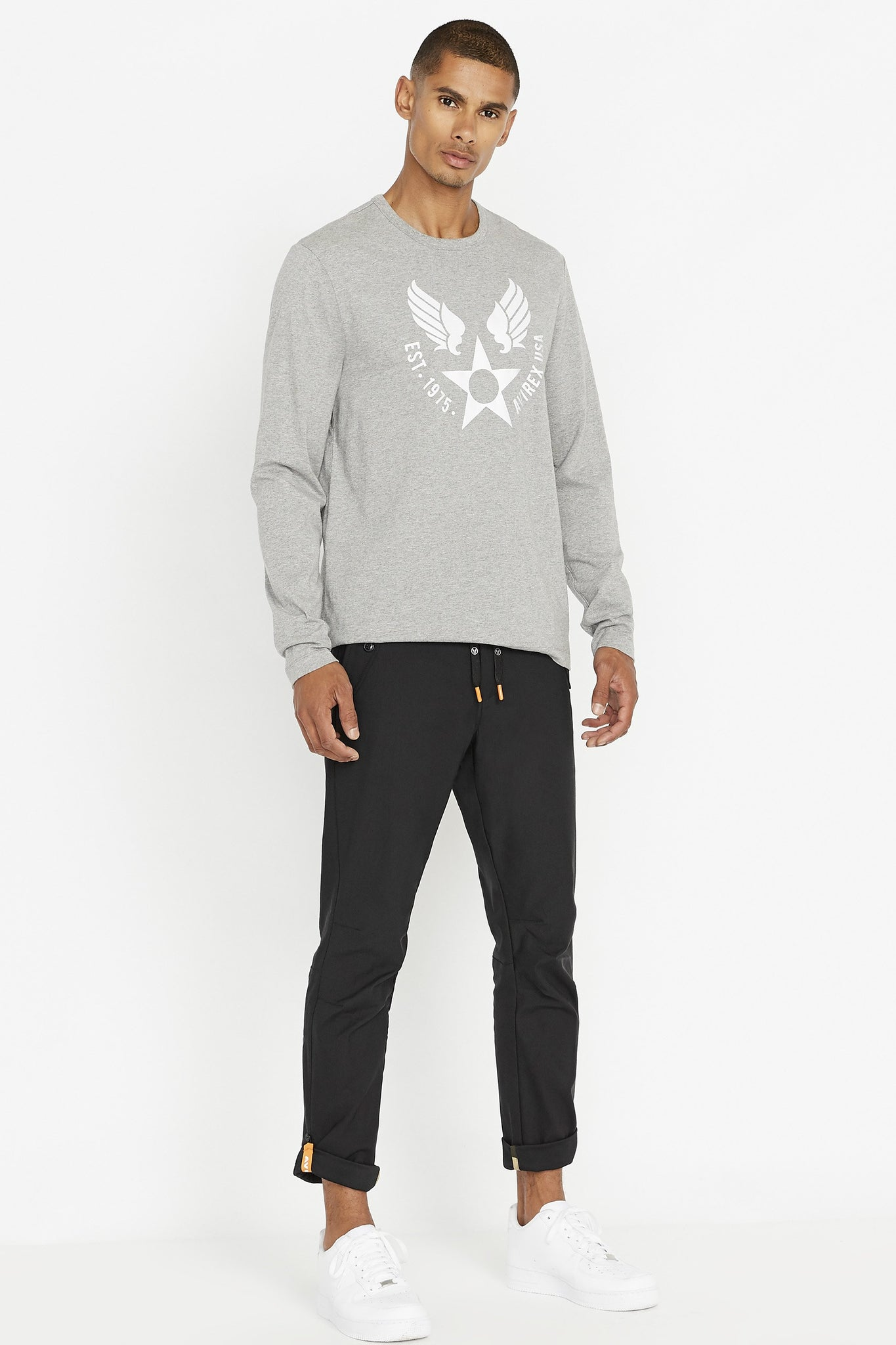 Full view of Men wearing a light grey long sleeve crew neck T-shirt with round logo graphic print on chest and black pants