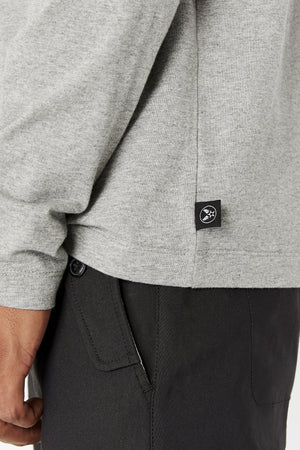 Detailed view of small black tag on the bottom side of T-Shirt