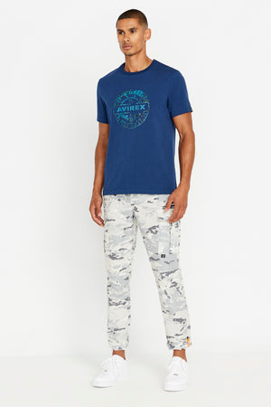 Full view of men wearing a blue short sleeve crew neck T-shirt with round logo graphic print on chest and grey camo print pants