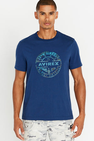 Men wearing a blue short sleeve crew neck T-shirt with round logo graphic print on chest
