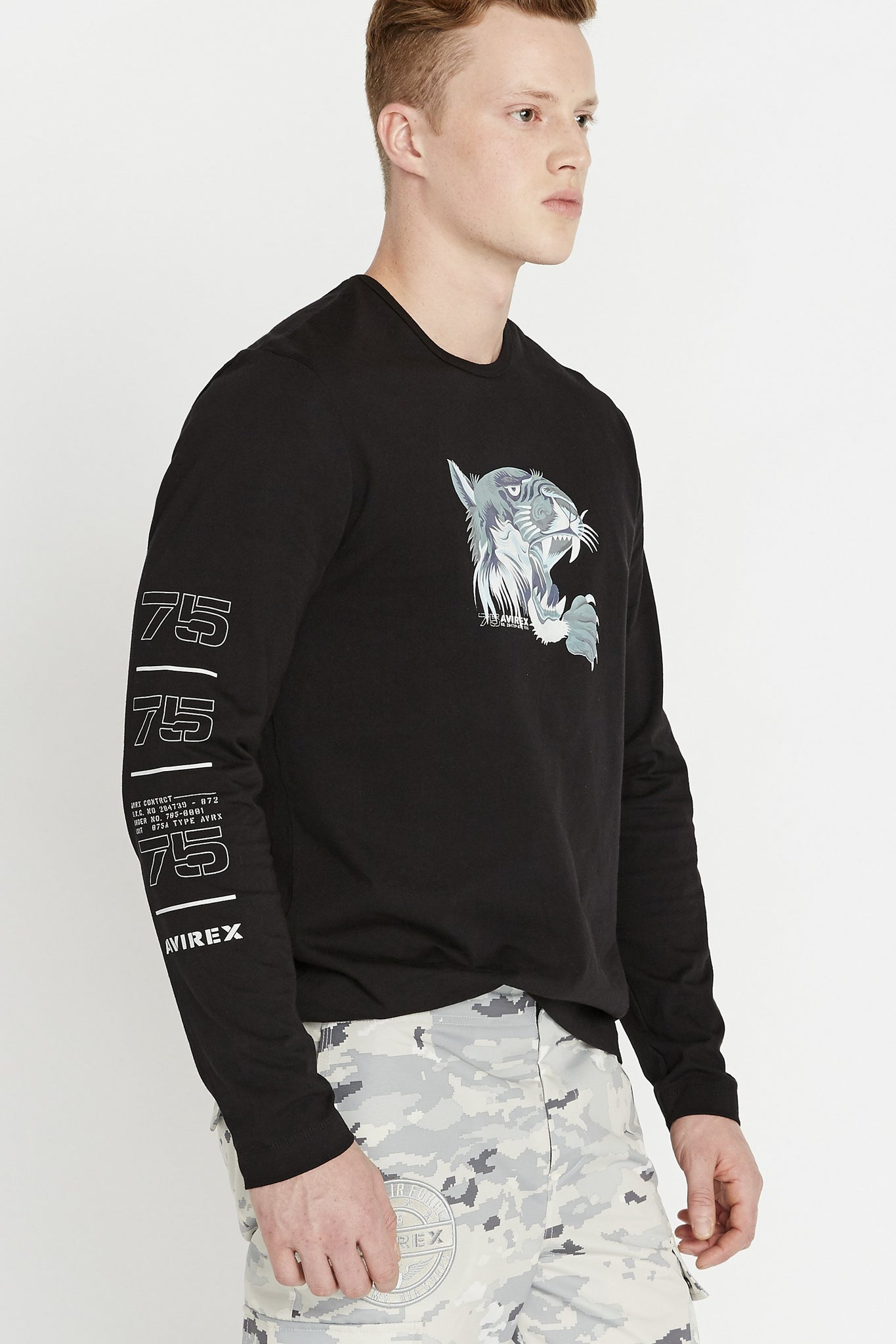 Side view of men wearing a black long sleeve crew neck T-shirt with light grey tiger print on chest and label print on sleeve