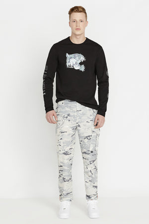 Full view of men wearing a black long sleeve crew neck T-shirt with light grey tiger print on chest and label print on both sleeves and grey camo print pants