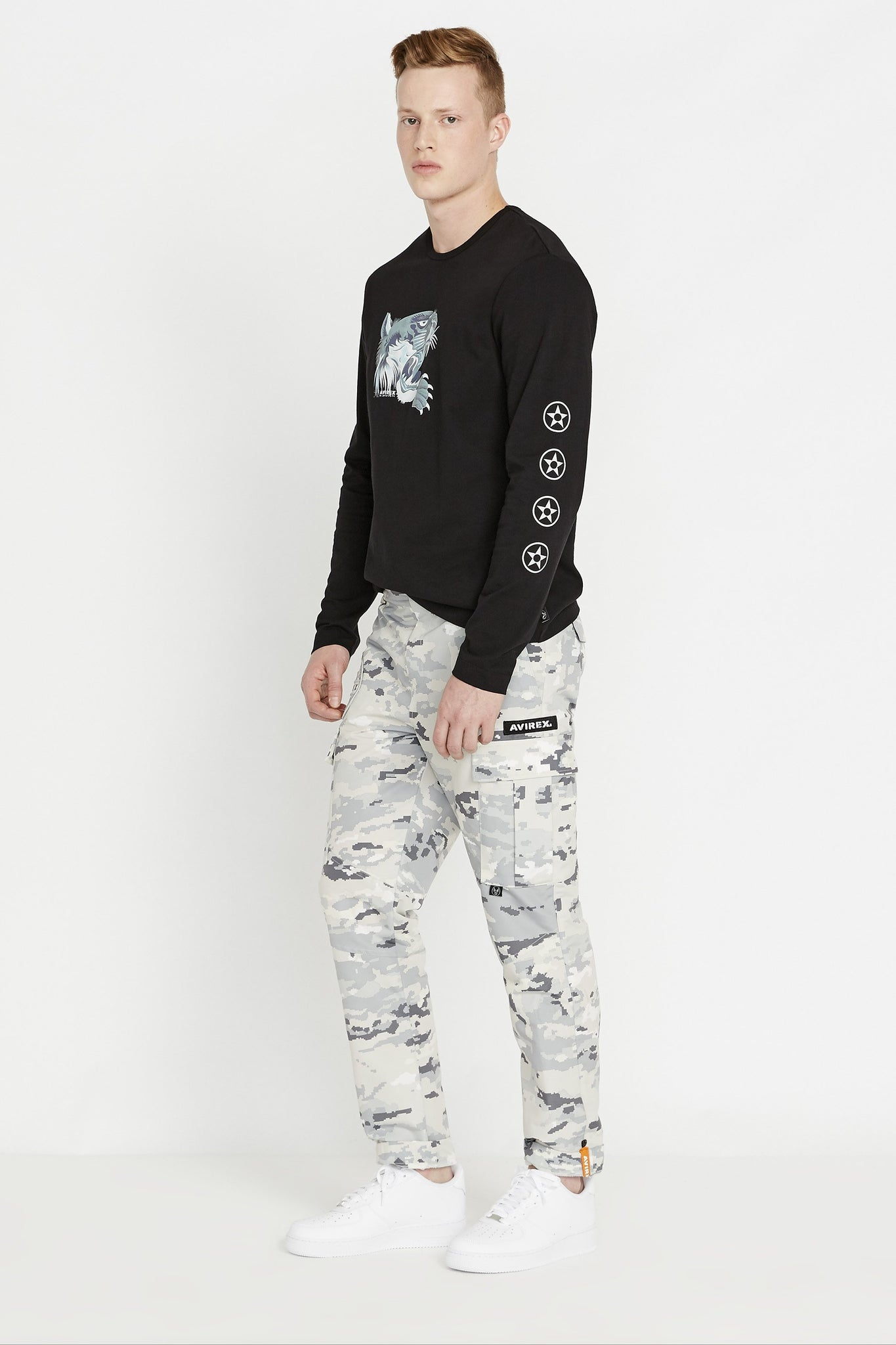 Side full view of men wearing a black long sleeve crew neck T-shirt with light grey tiger print on chest and label print on both sleeves and grey camo print pants