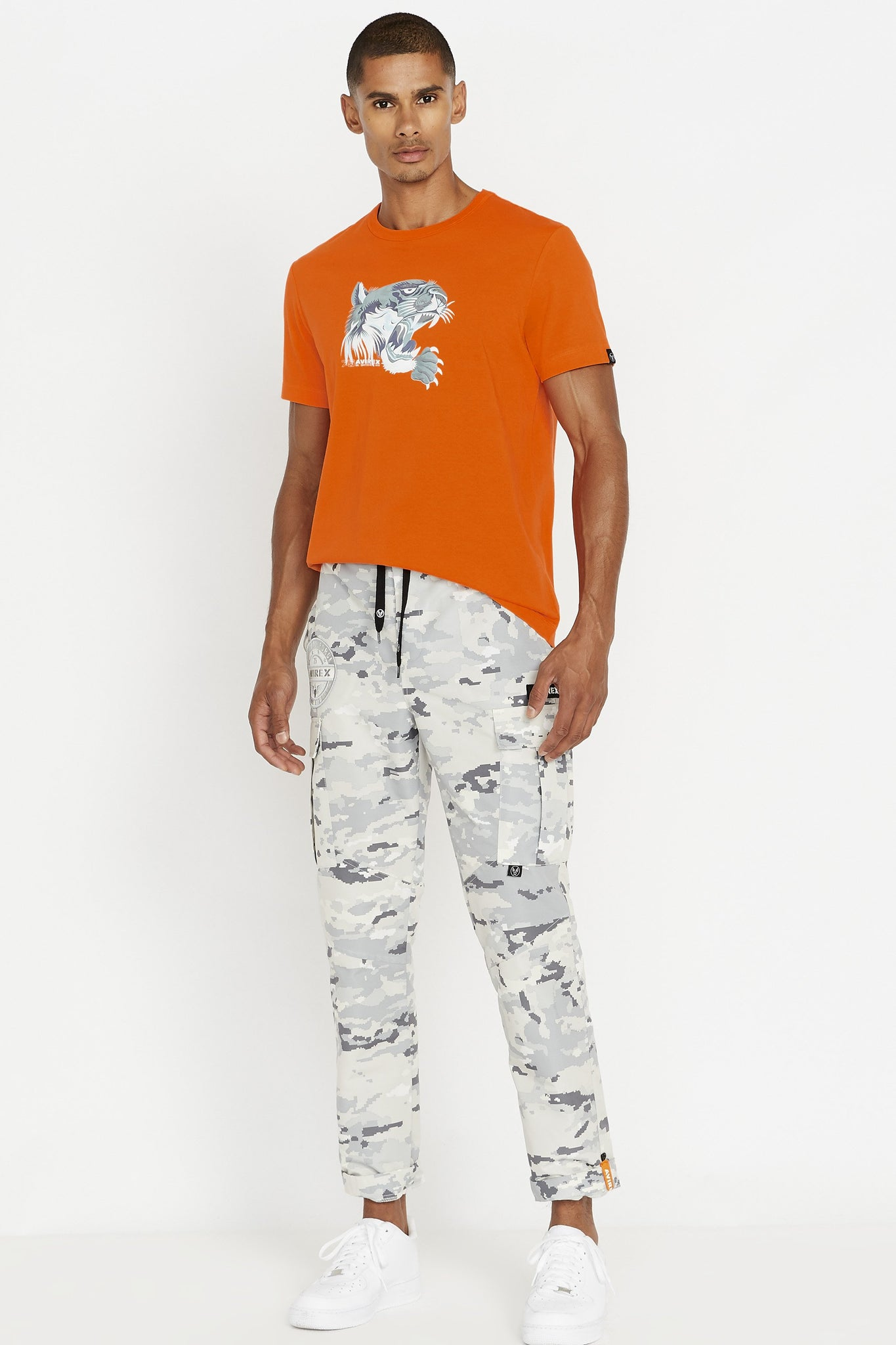 Full view of men wearing an orange short sleeve crew neck T-shirt with light grey tiger print on chest and light grey camo pants