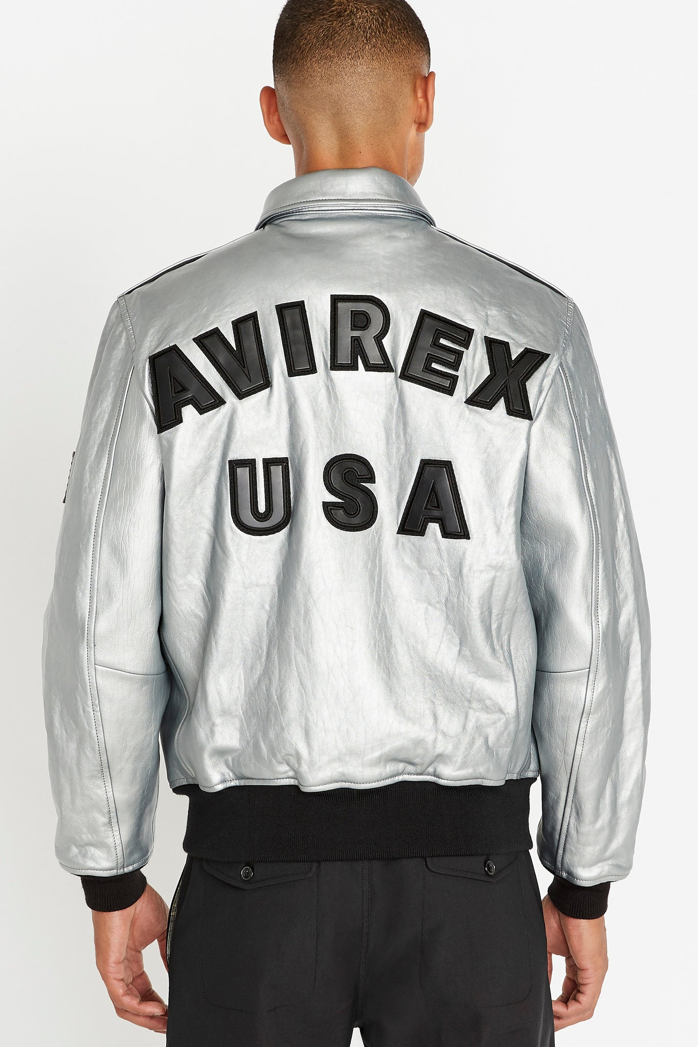 Back view of men wearing a silver leather bomber jacket with bold text lettering Avirex USA