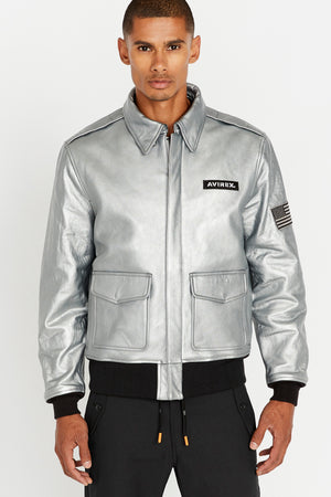 Front view of men wearing a fully zipped silver leather bomber jacket with snap down collar and two flap snap prockets, Avirex logo patch on the chest and one patch on the left sleeve