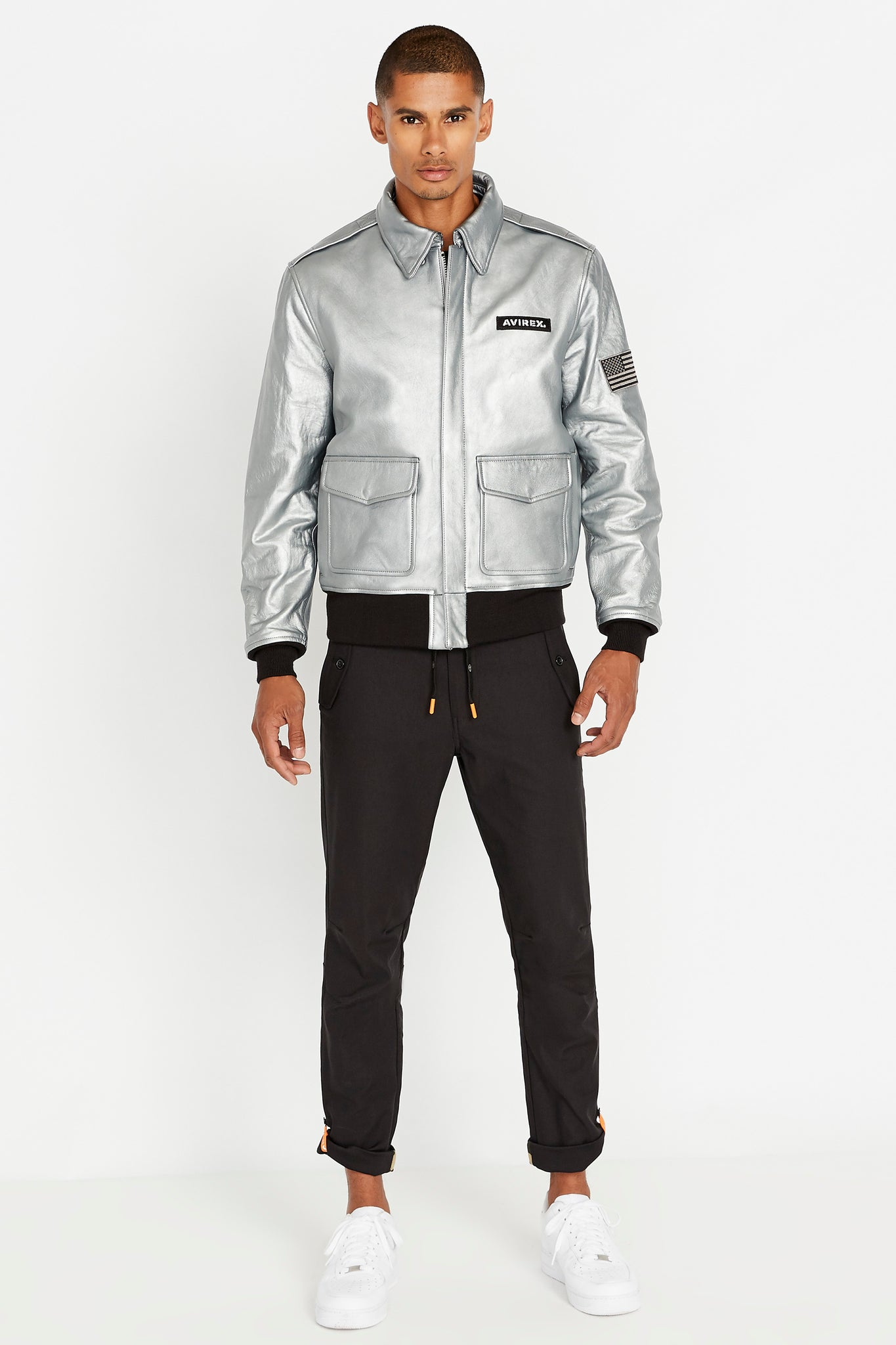 Full front view of men wearing a fully zipped silver leather bomber jacket with snap down collar and two flap snap prockets, Avirex logo patch on the chest and one patch on the left sleeve and black pants