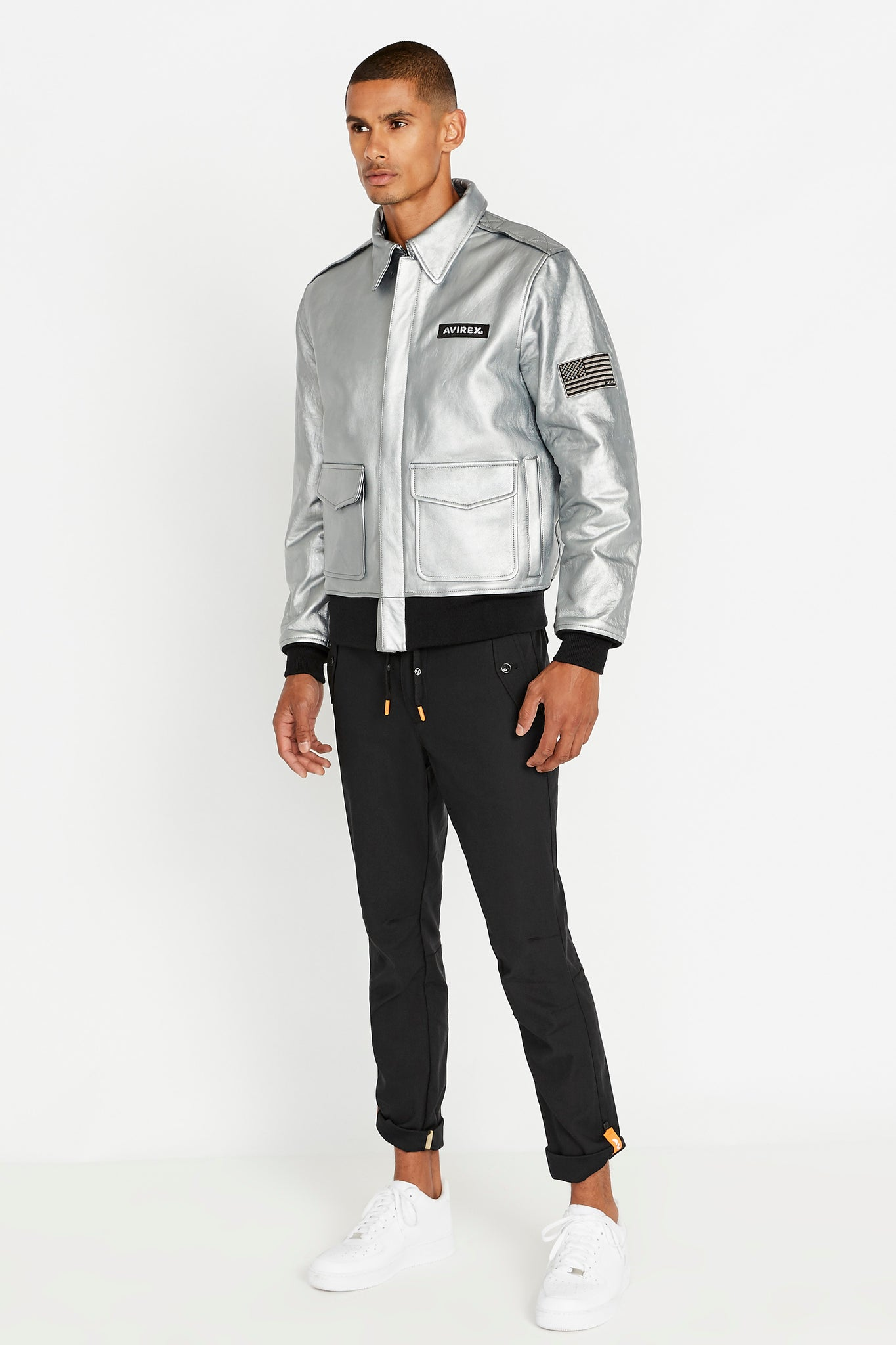 Full side view of men wearing a fully zipped silver leather bomber jacket with snap down collar and two flap snap prockets, Avirex logo patch on the chest and one patch on the left sleeve and black pants