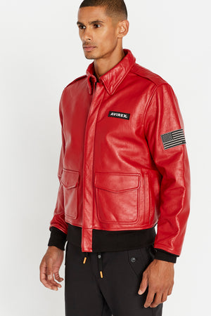 Side view of men wearing a fully zipped red leather bomber jacket with snap down collar and two flap snap prockets, Avirex logo patch on the chest and one patch on the left sleeve