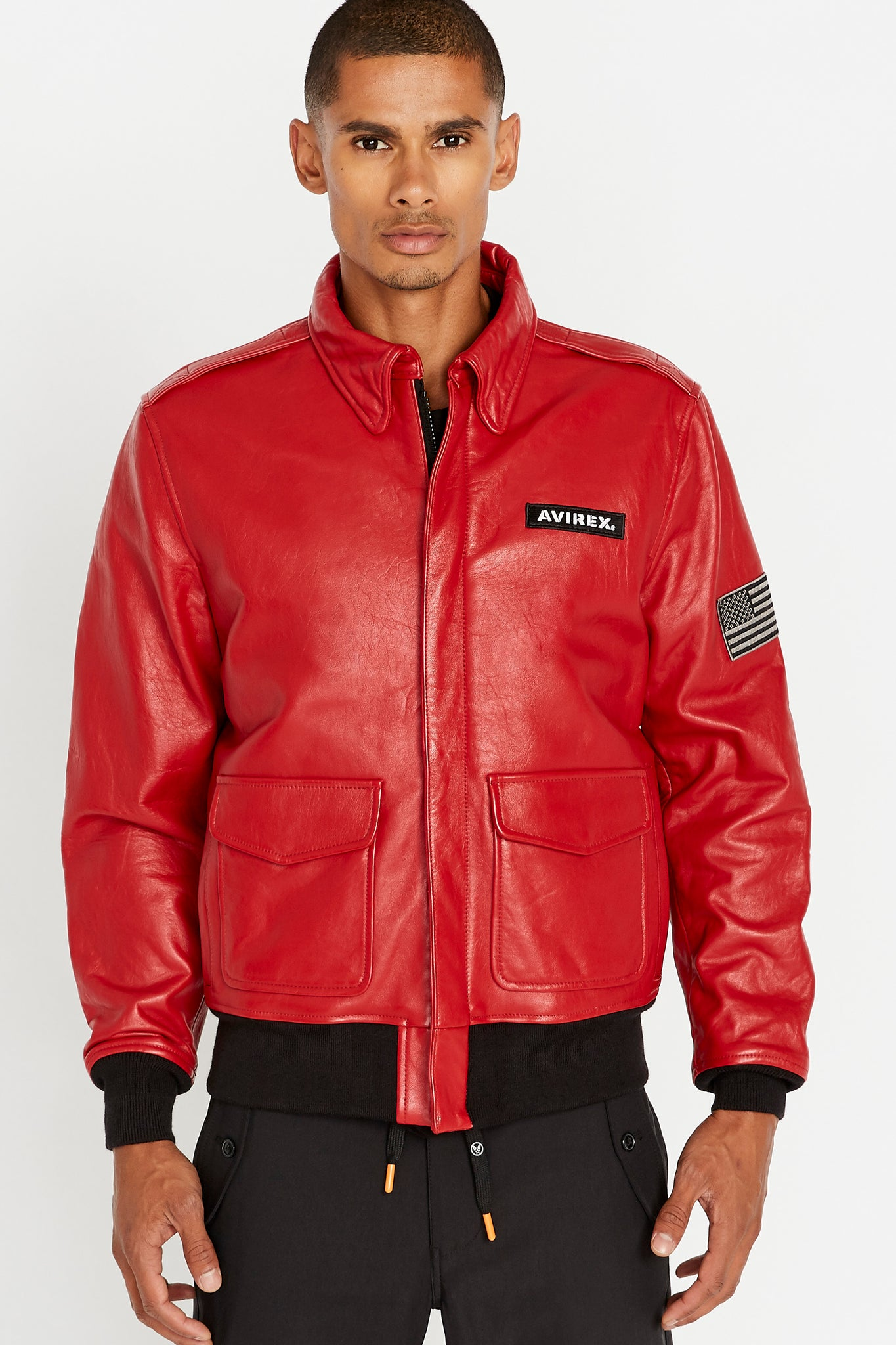 Front view of men wearing a fully zipped red leather bomber jacket with snap down collar and two flap snap prockets, Avirex logo patch on the chest and one patch on the left sleeve