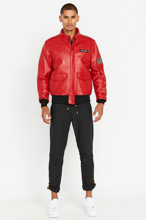 Full front view of men wearing a fully zipped red leather bomber jacket with snap down collar and two flap snap prockets, Avirex logo patch on the chest and one patch on the left sleeve and black pants