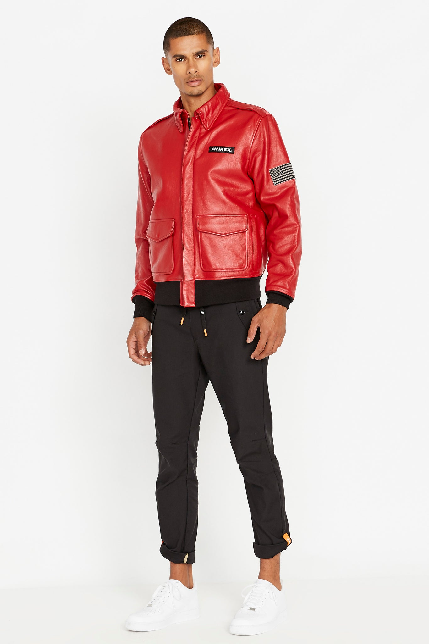 Full side view of men wearing a fully zipped red leather bomber jacket with snap down collar and two flap snap prockets, Avirex logo patch on the chest and one patch on the left sleeve and black pants