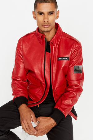 Front view of a sitting men wearing an open red leather bomber jacket with snap down collar and two flap snap prockets, Avirex logo patch on the chest and one patch on the left sleeve