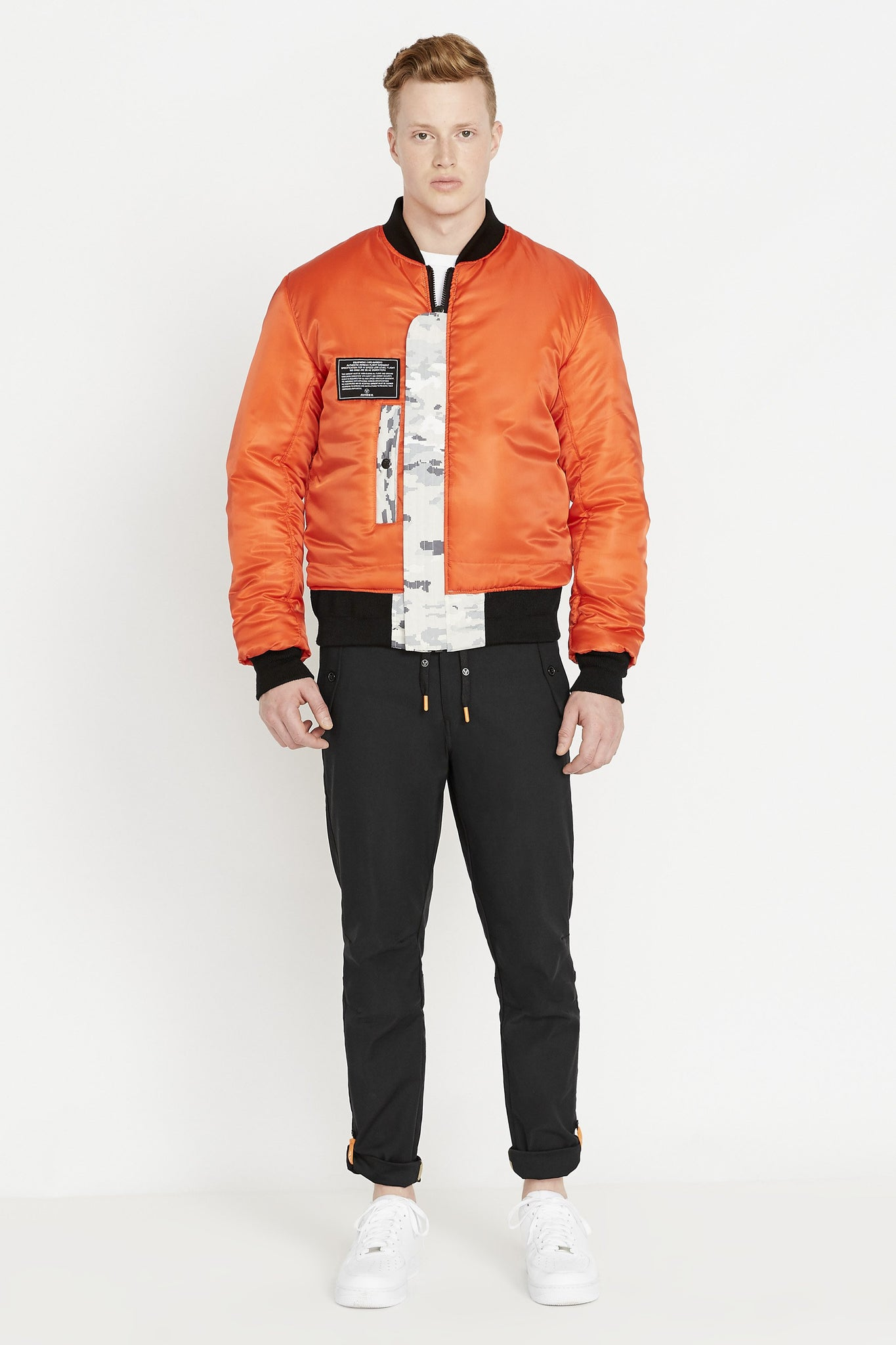 Full front view of men wearing a fully zipped reversed orange bomber jacket with one patch and one pocket on the right chest and black pants