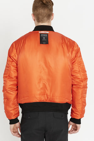 Back view of men wearing a reversed orange bomber jacket with one patch under collar