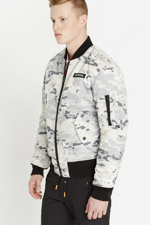 Side view of men weaing a fully zipped snow camo printed polyester bomber jacket with Avirex logo patch on the chest,  two flap pockets on the sides and one utility pocket on left sleeve