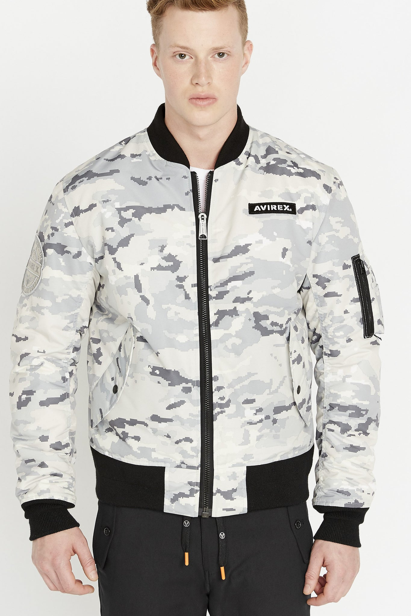 Front view of men weaing a fully zipped snow camo printed polyester bomber jacket with Avirex logo patch on the chest,  two flap pockets on the sides and one utility pocket on left sleeve
