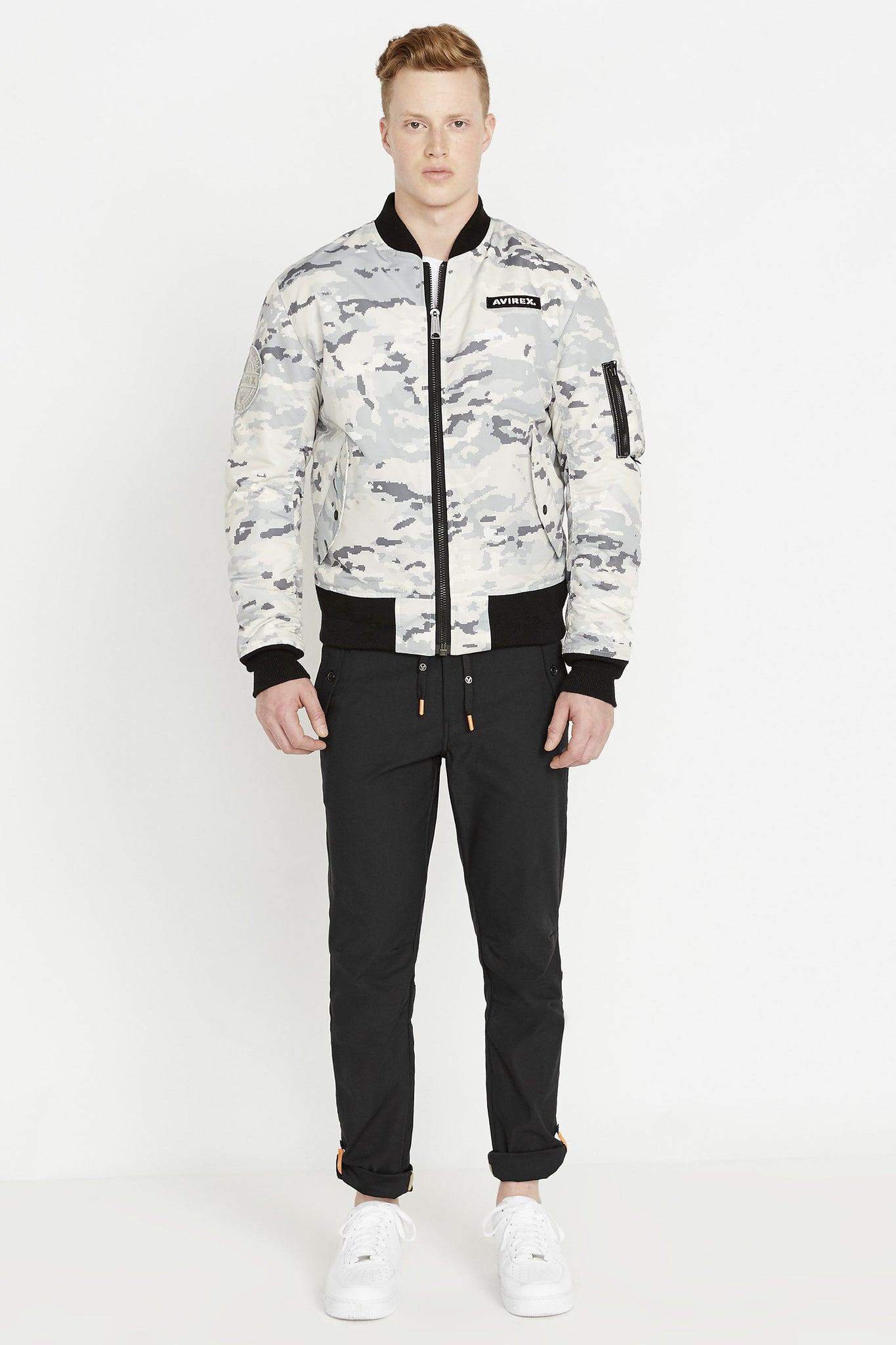 Full front view of men weaing a fully zipped snow camo printed polyester bomber jacket with Avirex logo patch on the chest,  two flap pockets on the sides and one utility pocket on left sleeve and black pants