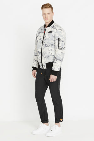 Full side view of men weaing a fully zipped snow camo printed polyester bomber jacket with Avirex logo patch on the chest,  two flap pockets on the sides and one utility pocket on left sleeve and black pants