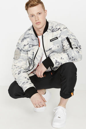 Front view of a crouching man with an open snow camo printed polyester bomber jacket with black pants