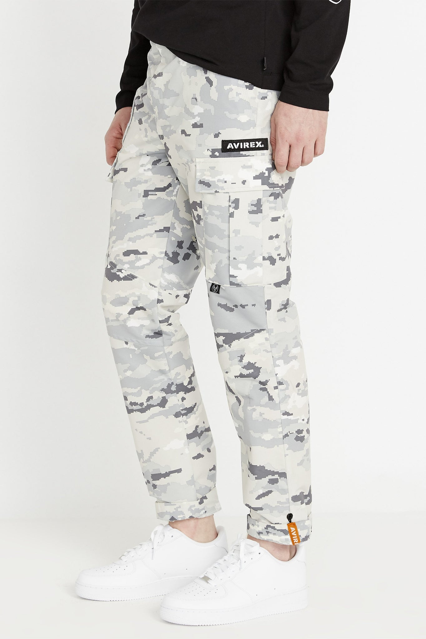 Side view of digital snow camo print pants with Avirex patch above side cargo pockets and rolled up hem with reflective logo