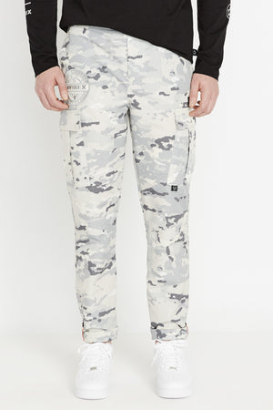 Front view of digital snow camo print pants with round logo patch above side cargo pockets and rolled up hem with reflective logo