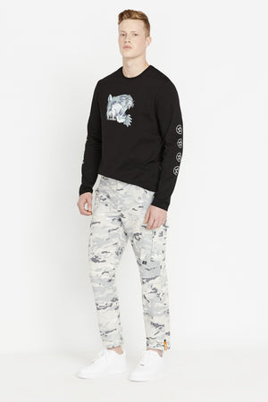 Side full view of men wearing a digital snow camo print pants with side cargo pockets and black long sleeve crew neck sweater