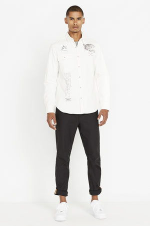 Full view ofMen wearing a white long sleeve shirt with one front button-flap pocket on the right chest with embroidery logo above that and embroidery tiger on left chest embroidery patch on right bottom corner