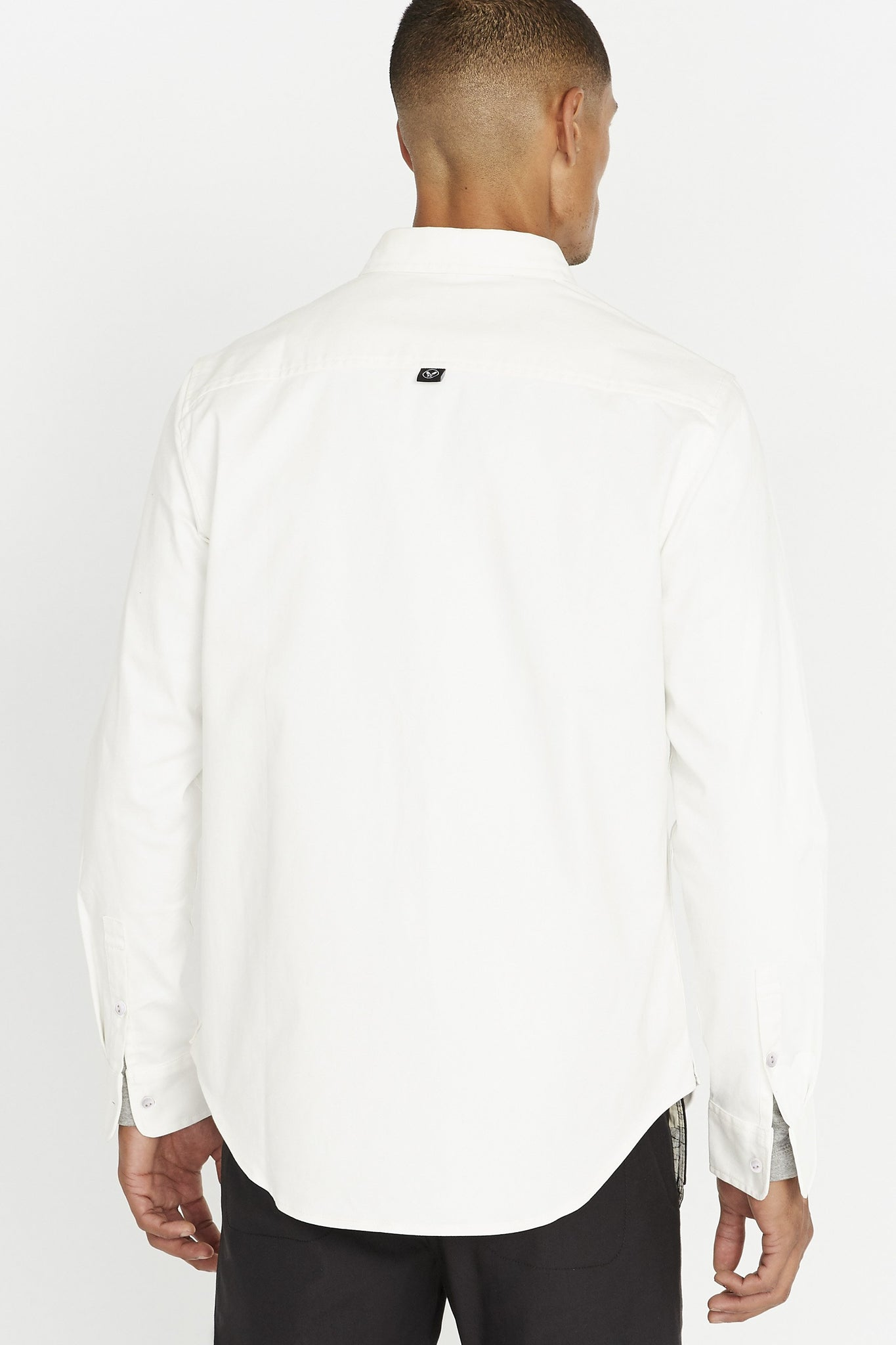 Back view of men wearing a white long sleeve shirt with two buttons on each sleeve and small tag on the back middle