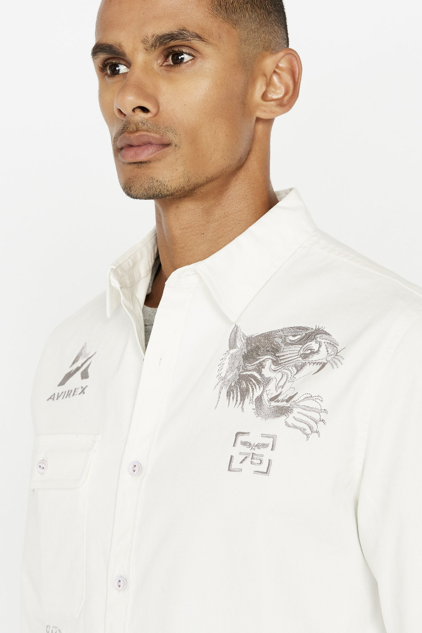 Detailed view of embroidery logo above pocket on right chest and embroidery tiger on the left chest