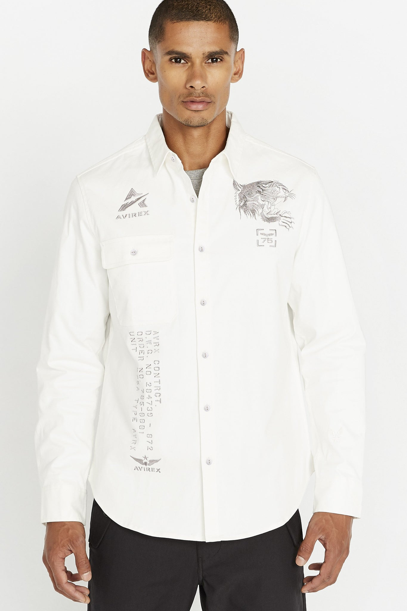Men wearing a white long sleeve shirt with one front button-flap pocket on the right chest with embroidery logo above that and embroidery tiger on left chest embroidery patch on right bottom corner