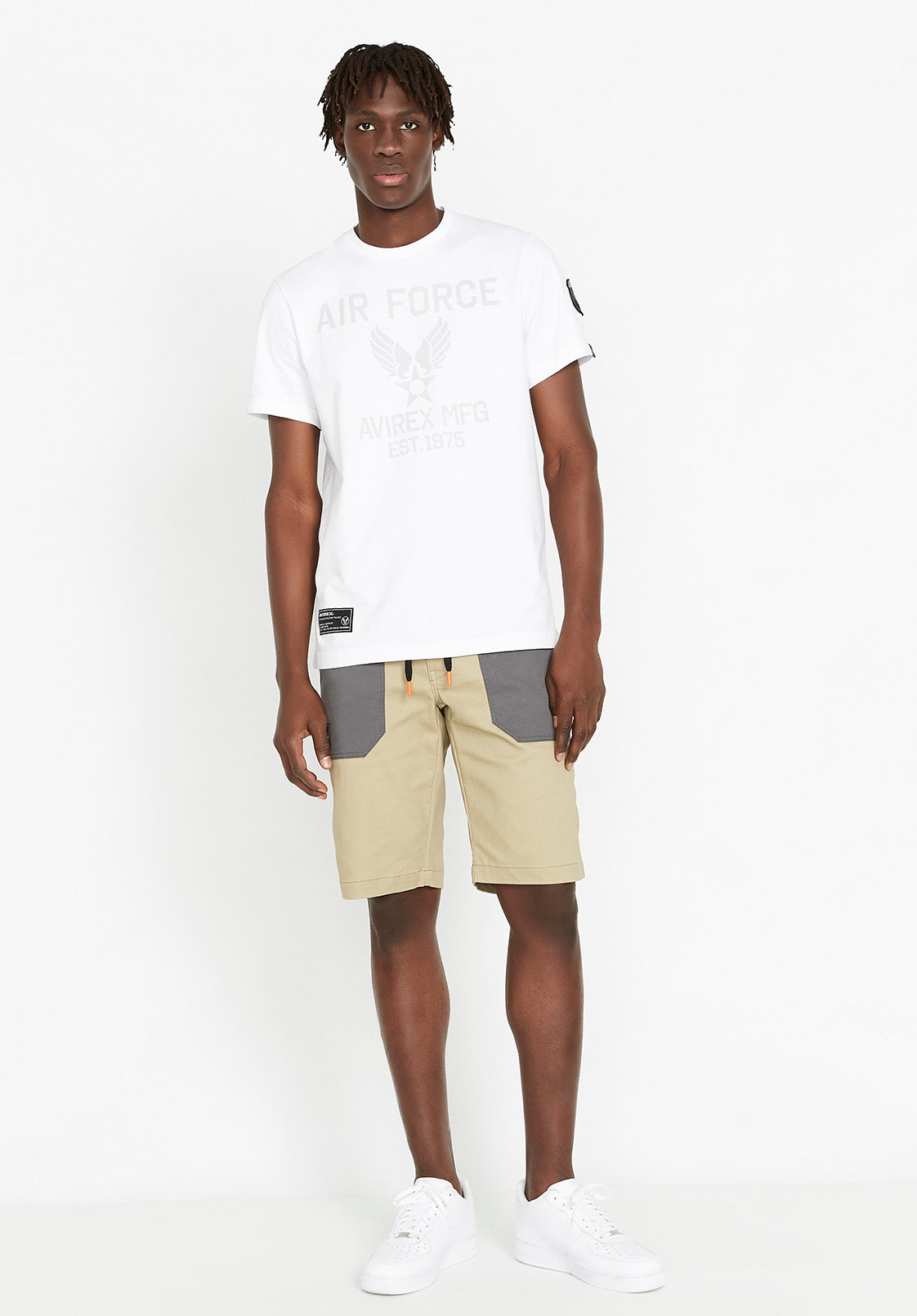 Full view of men wearing a white t-shirt with Avirex Air Force logo print in light grey with beige shorts