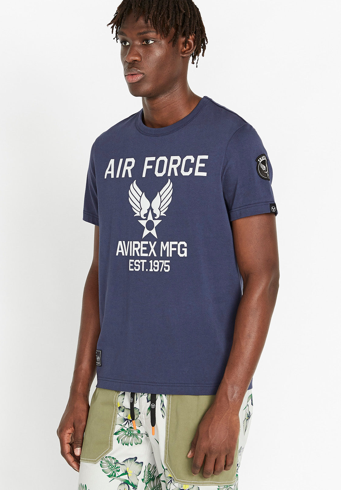 Side view of men wearing an indigo t-shirt with Avirex Air Force logo print in light grey and side Wingstar patch on left arm