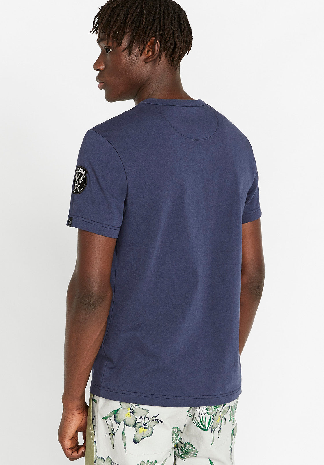 Back view of men wearing an indigo t-shirt with Wingstar patch logo on left arm