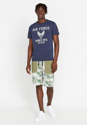 Full view of men wearing an indigo t-shirt with Avirex Air Force logo print in light grey with flower print shorts
