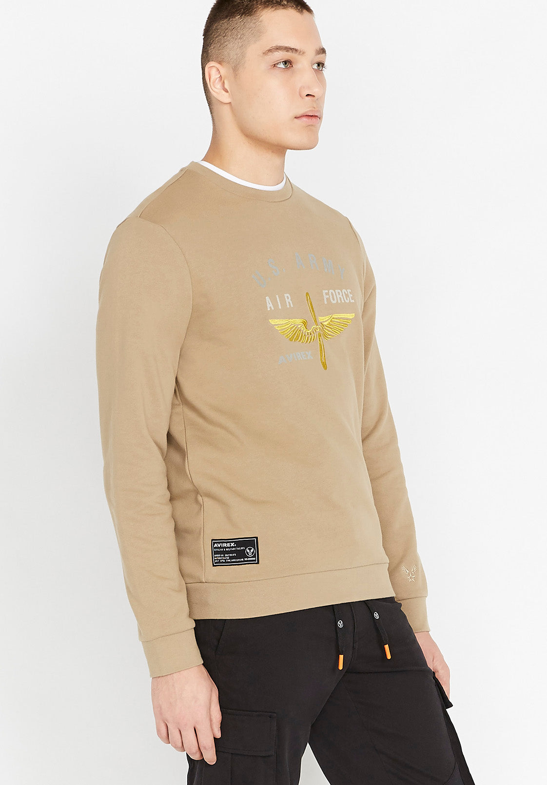 Side view of men wearing a beige long sleeve crew neck sweater with front US Army white and yellow logo and black side patch on right bottom corner