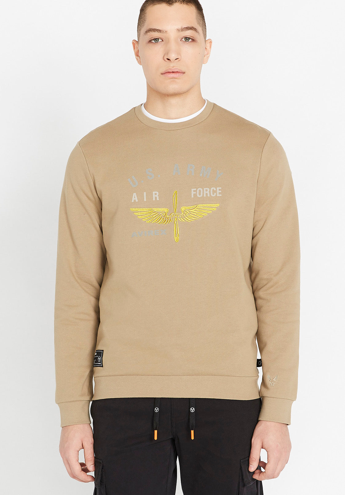 Men wearing a beige long sleeve crew neck sweater with front US Army white and yellow logo