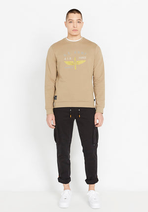 Full view of men wearing a beige long sleeve crew neck sweater with front US Army white and yellow logo and black pants